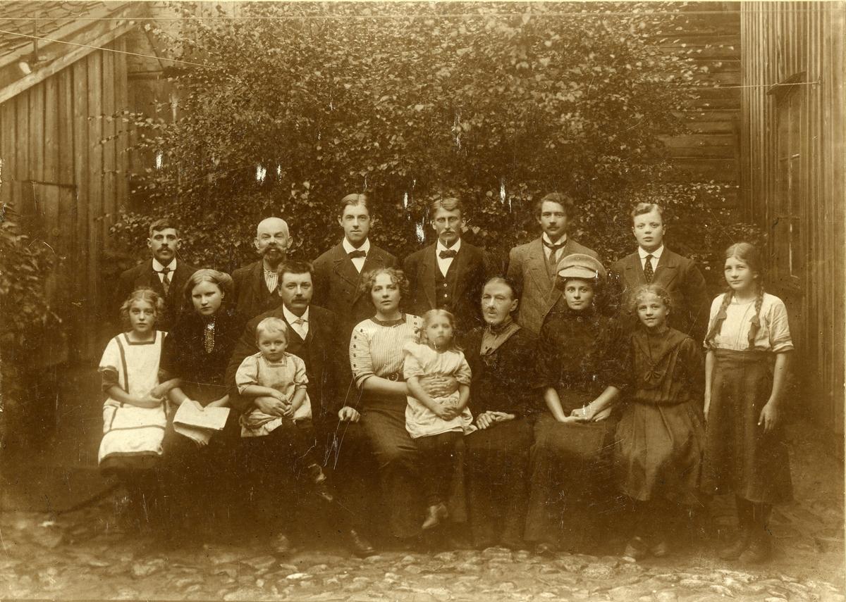 """""""Løkkebergs hotel for reisende"""", drevet av Hulda Løkkeberg, Bakgaten (senere Farmannsgaten) 7, Vestre Fredrikstad. Første rekke (fv): Tore Løkkeberg (gift Segelcke) (1901-1979), en tjenestepike, Hulda Marie Løkkeberg (f. Hansen)(1878-1941) med datteren Hulda på fanget), fru Løkkeberg (Georg Løkkeberg sen. mor), fru skreddermester Charlotte Enger med datter, Harda Løkkeberg. Annen rekke (fv): Ukjent tyopgraf, en tysk typograf, O. G. Husa (typograf), Filip Skogstrøm (typograf), Leif Moen (fra Bergen), sønn av Alfred Løkkeberg, Oslo. Samtlige i bakre rekke er typgrafer. - Georg Løkkeberg sen. (1872-1951) var maskinmester i Fredriksstad Blad. Privatbilde tatt av omreisende fotograf i 1912."""