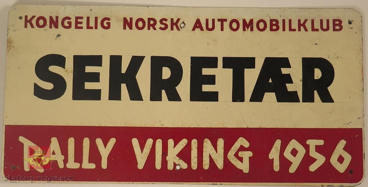 Hovedsakelig hvitt metallskilt med et mindre rødt markeringsområde. Det er laget til 6 festehull på skiltet, 3 nede og 3 oppe. Påskrift: KONGELIG NORSK AUTOMOBILKLUB, SEKTRETÆR, K.N.A. RALLY VIKING