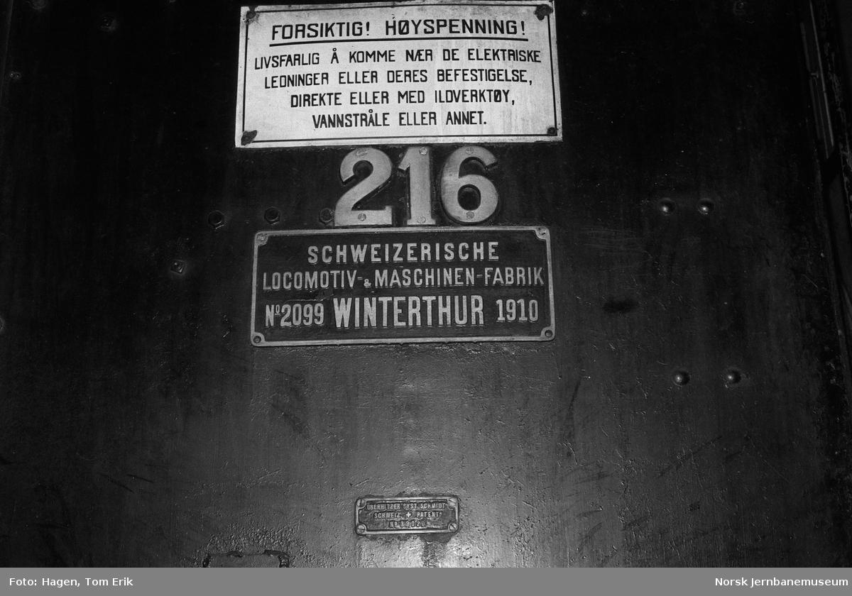 Fabrikk- og nummerskilt på damplokomotiv 26a 216 i lokomotivstallen på Hamar