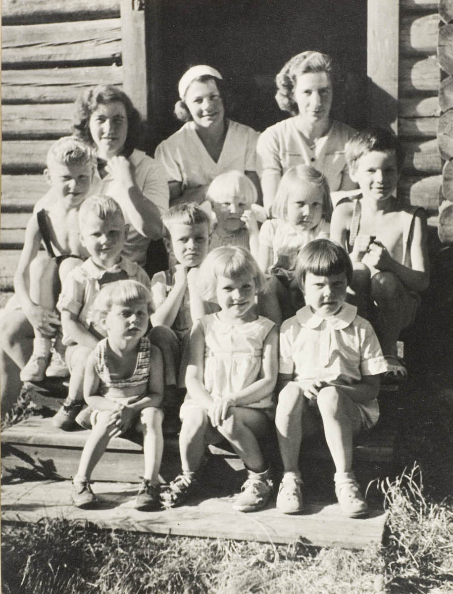 Tre voksne damer og ni barn sittende på trapp, sommer, tømmerhus