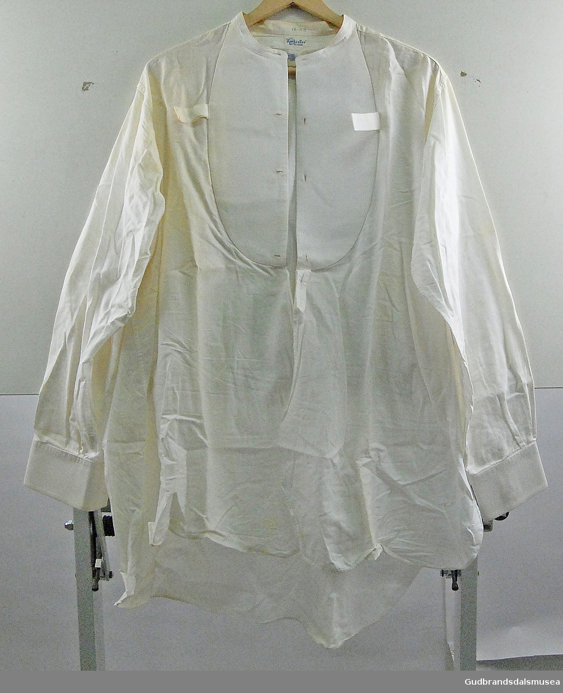 Hvit skjorte, mann, med stivet skjortebryst/bryststykke og brede kanter på ermene. Skjortebrystet har knappehull og åpning går helt ned. Tre hemper i front og en i nakke.