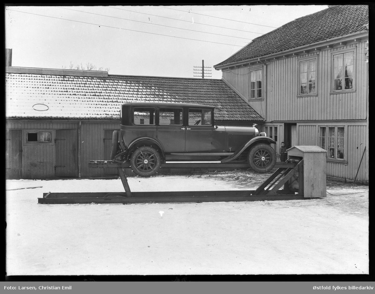 John Dahles bilverksted, bakgården til St. Marie gate 112 i Sarpsborg. Bil står på en smørebukk, ørn på panser, dekk merket Oakland, kjetting på bakhjul. Ukjent gutt.   Bygningen til høyre er St. Mariegate 112. John Dahle hadde bilverksted her fra 1920 til 1932. Bygningen brant i 1935 og det ble satt opp nytt verksted. A/S Østlandsk Auto startet opp i de nye lokalene.(Kilde: St. Mariegate gjennom tidene).