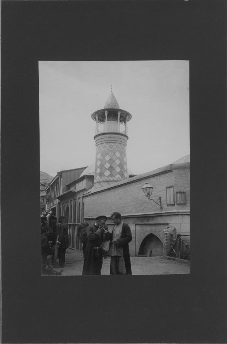 'Gatuvy, i förgrunden män och barn. Bakom dem byggnad med torn. ::  :: Ingår i serie med fotonr. 5288:1-30. Se även fotonr. 5269-5292 med bilder från Stuxbergs resa till Kaukasien.'