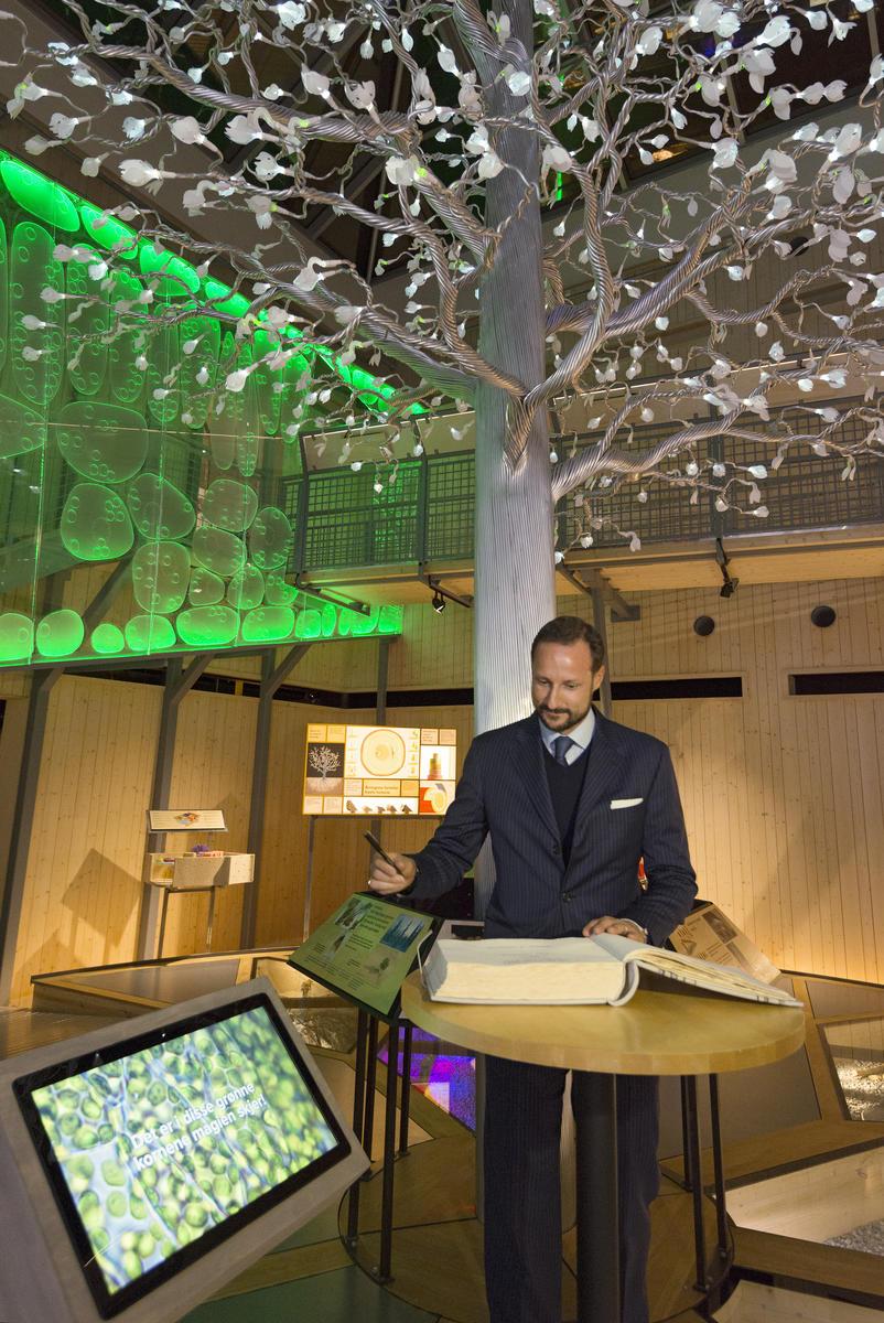 """Kronprins Haakon signerer gjesteboka under åpningen av utstillingen """"Det fantastiske treet"""" 26/1 2016"""