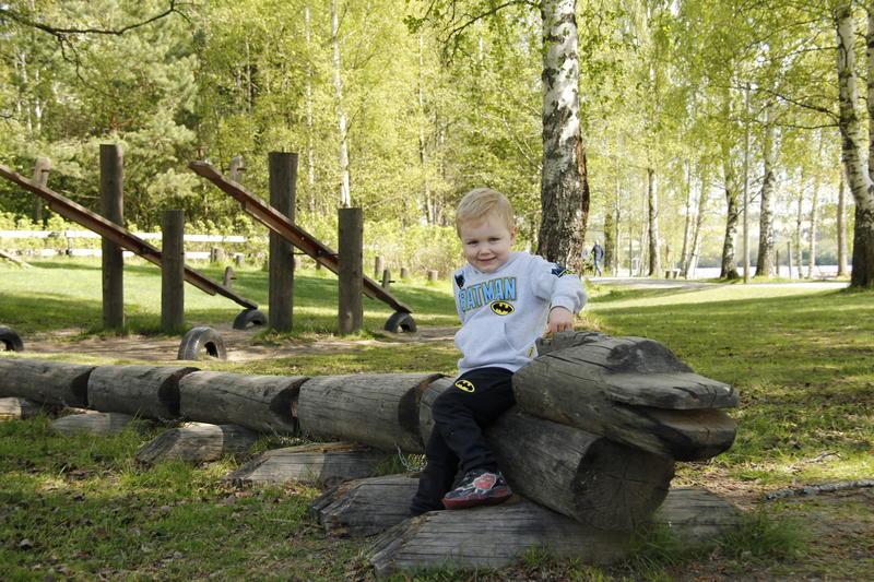 Liten gutt sitter på tømmer i lekeparken på Fetsund lenser