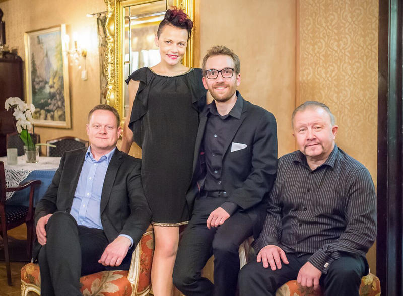 Tre menn og ei dame i ei stue