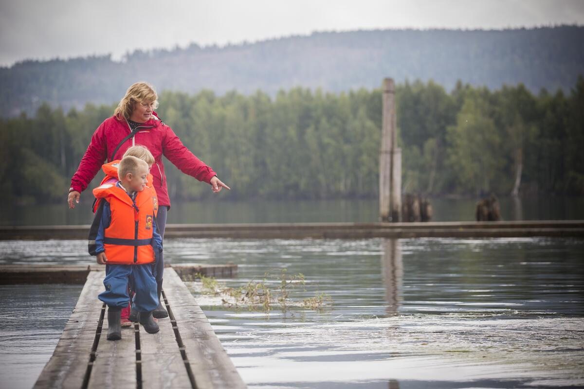 En voksen dame og to små barn går på flåteganer i elva. Begge barna har oransje redningsvester på seg. (Foto/Photo)