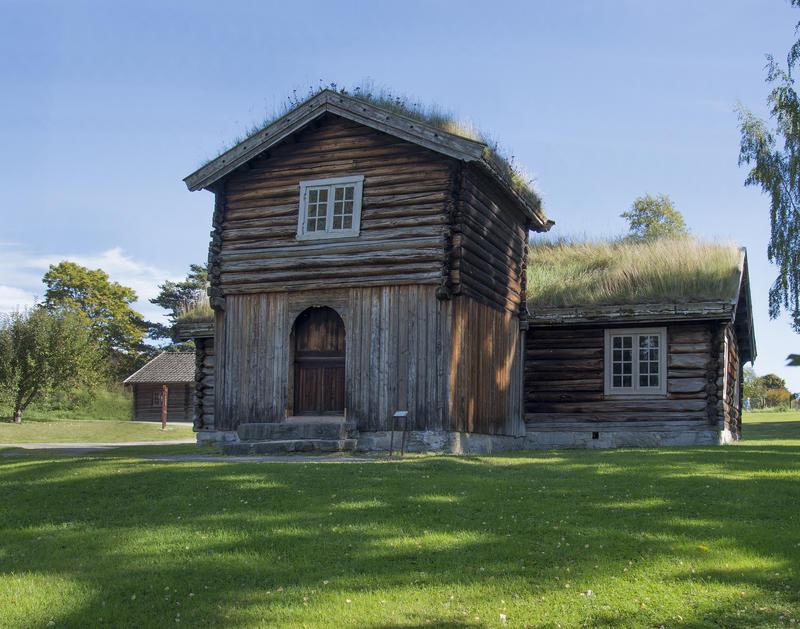 """Lav, grå tømmerbygning med gress på taket og toetasjers tilbygg, et såkalt """"barfrø"""" midt på langveggen."""
