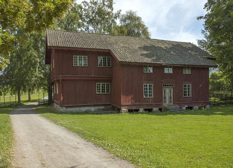 Stor, rød, plankebeslått bygning i to etasjer.