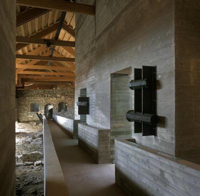 Sverre Fehns betongbro gjennom museets middelalderdel er omkranset av funn fra ruinene etter bispegården, blant annet kanonfragmenter.