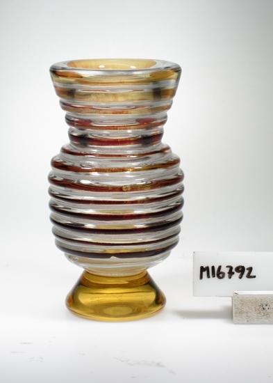 """Vas, s.k """"Edvin-glas"""", överfångsglas. Konstnär: Edvin Öhrström. Tekniken """"Edvinglas"""": Ett ariel-ämne tillverkas, men det blåses inte upp till en ariel (då man """"kränger"""" ett lager ofärgat glas över ämnet, så att luftbubblor bildas, för att sedan forma det till önskat föremål) utan man formar själva ämnet som det är. På så sätt får man ett föremål med kraftig relief. Beskrivning: Konisk fot. Närmast äggformad kropp. Konad hals. Kroppen och halsen horisontalräfflade.  Färg: Ofärgad med gult till rödskiftande överfång. Klarglas. De horisontala ränderna guldgula längst upp och övergår sedan till rödbrunt på kroppen. Foten guldgul. Teknik: Blåst, drivet, överfång, kulad, blästrat mönster, uppvärmt. Mått: Diameter ovan avser vasens övre diameter. Fotdiameter: 54 mm. Ristad signering i botten. Se """"Signering, märkning"""" ovan. Inskrivet i huvudkatalogen 1959.  Registerkortet skrivet 1975, dubblett? Funktion: Vas"""
