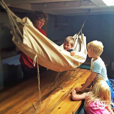 Hengekøye ombord skip, ett barn i hengekøya, to barn utenfor, én voksen bak.