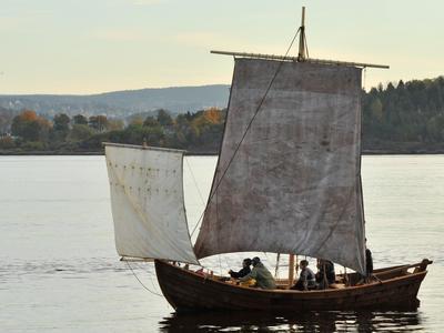 Trebåten Vaaghals på vannet med to seil, minst fem personer ombord, kveldssol, land i bakgrunnen.