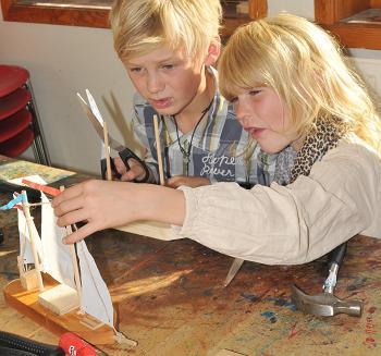 Barn som bygger seilbåt i barnas båtverksted på Norsk Maritimt Museum. Foto/Photo