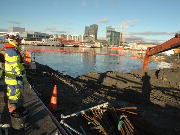 Arkeologene graver, Bjørvika og byen i bakgrunnen.. Foto/Photo