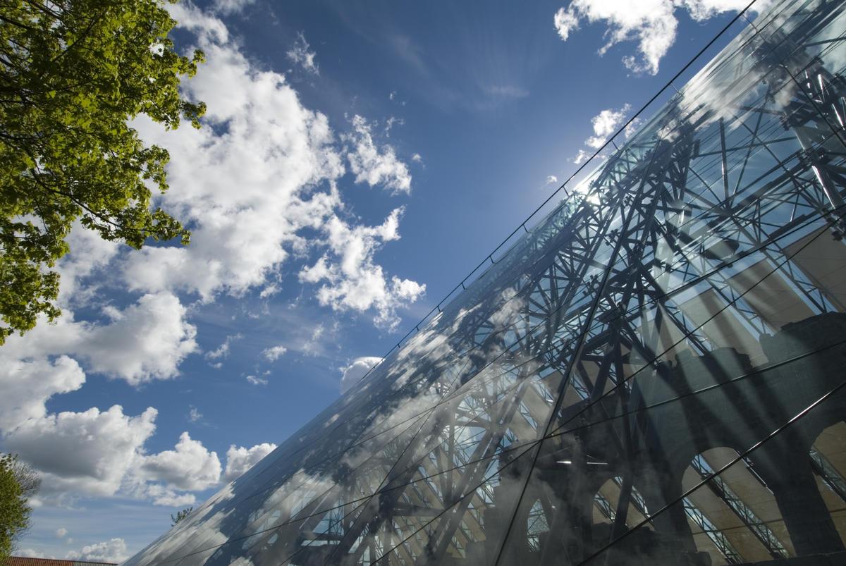 Hvite skyer speiler seg i glasset på vernebygget mens silhuetten av domkirkeruinen skimtes bak glasset. (Foto/Photo)