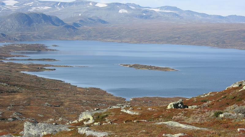 Innsjøen Vinstre sett fra Dragarskaret, i forgrunnen steiner og brunt gras, fjell med litt snø i bakgrunnen.