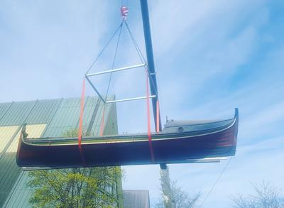 Trebåt heises opp i lufta med kran utenfor Båthallen.