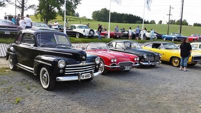 Mange biler oppstilt som utstilling på en parkeringsplass.  Mennesker som går og ser på bilene.