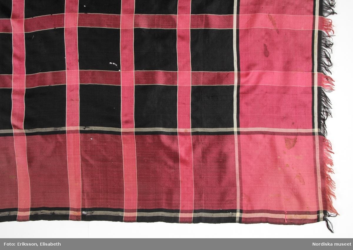 Kvadratiskt halskläde av siden i kypert. Svart botten med inrutning med rosa ränder med vit kontur och 13 cm bred kantbård i samma rosa färg,  runtom alla sidor upprispad kort frans. Anm. Något blekt  i 2 av hörnen samt några fläckar /Berit Eldvik 2011-11-16
