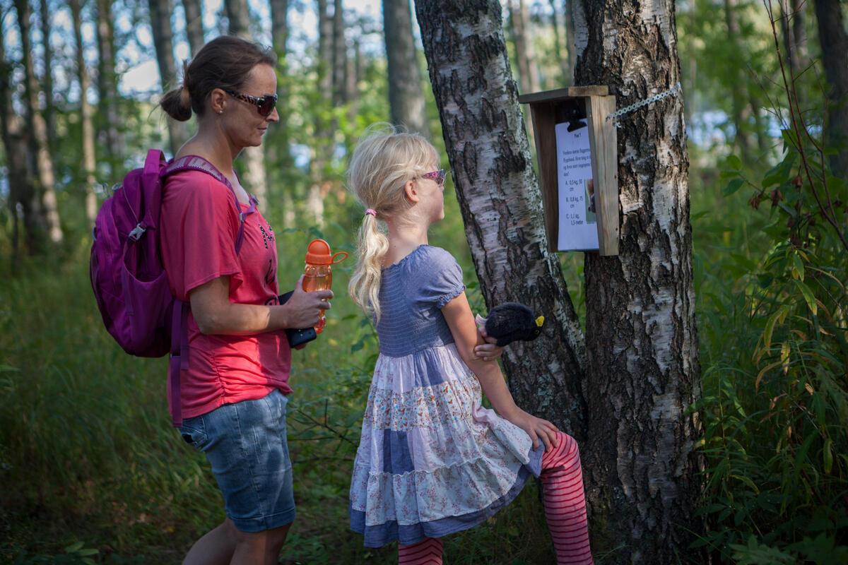 Mor og datter leser på en naturstipost på Blikomøya. Mor har olabukse og t-skjorte på seg og datteren har sommerkjole (Foto/Photo)