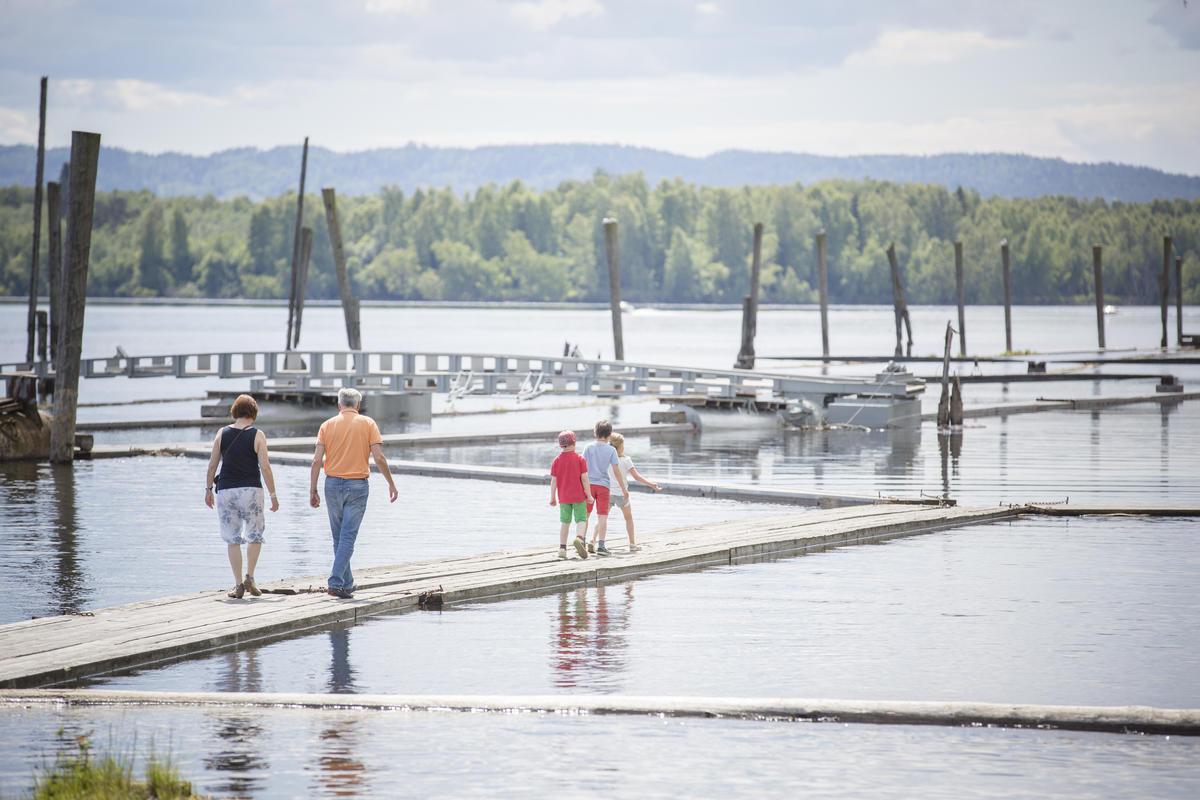Familie som går på flåtegangene i sorteringsanlegget. Mor, far og tre barn