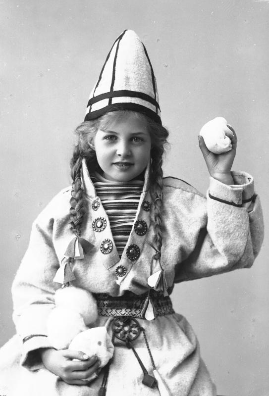 Pike i sameliknende drakt med kofte, lue og belte. I hendene holder hun juksesnøballer. 1908. (Foto/Photo)