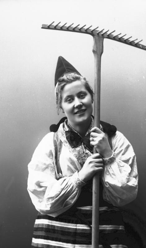 Kvinne i drakt og lue, som holder rive. 1908. (Foto/Photo)