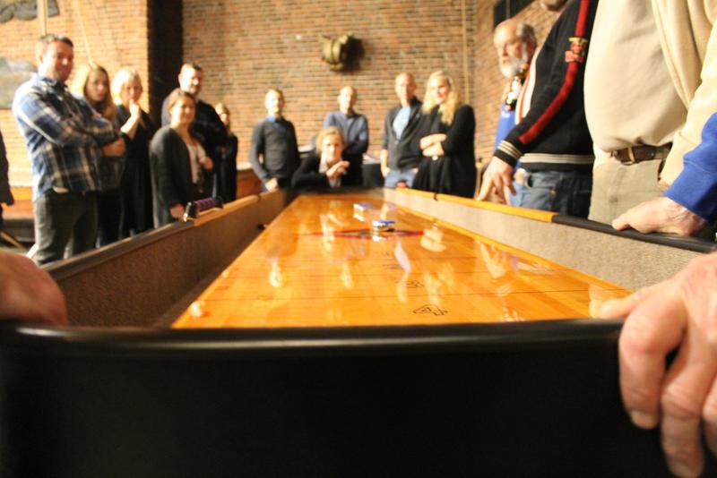 Shuffleboard i vestibylen på Norsk Maritimt Museum, nærbilde av den ene enden, mange folk rundt. (Foto/Photo)