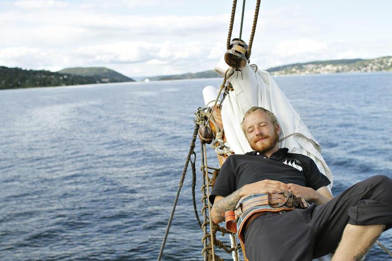 """Mann slapper av ombord skonnerten """"Svanen"""", blått vann, land og klar himmel i bakgrunnen. (Foto/Photo)"""