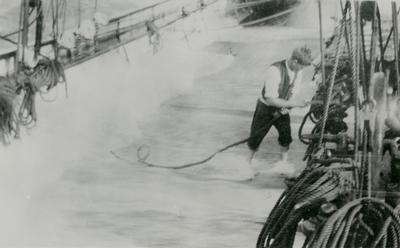Person i arbeid på dekk i høy sjø.