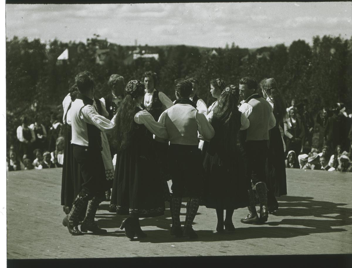 Kvinner og menn i bunader danser leikaring..