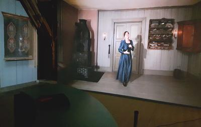 Bilde fra utstillingen BAR1567 hvor man ser en videoprojeksjon av Madam Guldberg som ønsker besøkende velkommen.