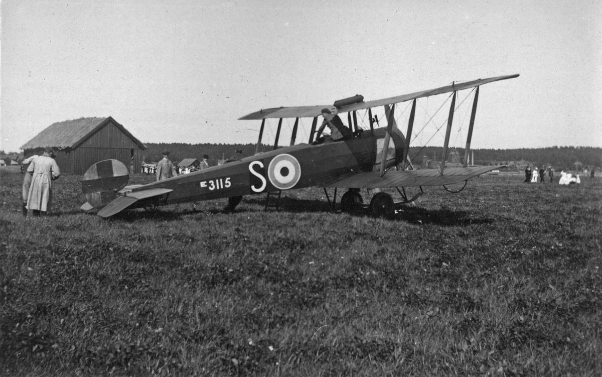 Ett flygplan på Ullviängar under en flyguppvisning den 5 augusti 1919. I bakgrunden åskådare och en lada. Piloten är den brittiske stridsflygaren Major Cecil Johnstone, som visar upp flygplanets färdigheter. Piloten var inhyrd av P. O. Flygkompani som ägdes av Fältflygarlöjtnanten P. O. Herrström. I Köpings Posten, står, att det var första gången en flygmaskin landat i Köping. Planet var ett Avro 504K, brittiskt jakt- och skolflygplan, med beteckningen E 3115. Flygplanet väckte sensation, och många tog sig dit, men stadens cyklister, väckte däremot stadens harm. Cyklisterna bråkade med fotgängarna om rätten till vägkanterna, som tvingades ut i vägen. Allt enligt en upprörd skribent på Köpingsposten.  Givare H. Bergendahl.