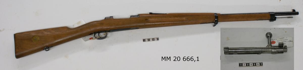 """Gevär med tillbehör. :1Gevär av blånerat stål, kolv av trä. Individnummer 189839. Slutstycke: 839. Stämplar på pipan: """"Gustafs Stads Gevärsfaktori 1906"""" samt krona. Krönt sikte. Bricka på kolv för angivning av ammunition: torpedammunition."""