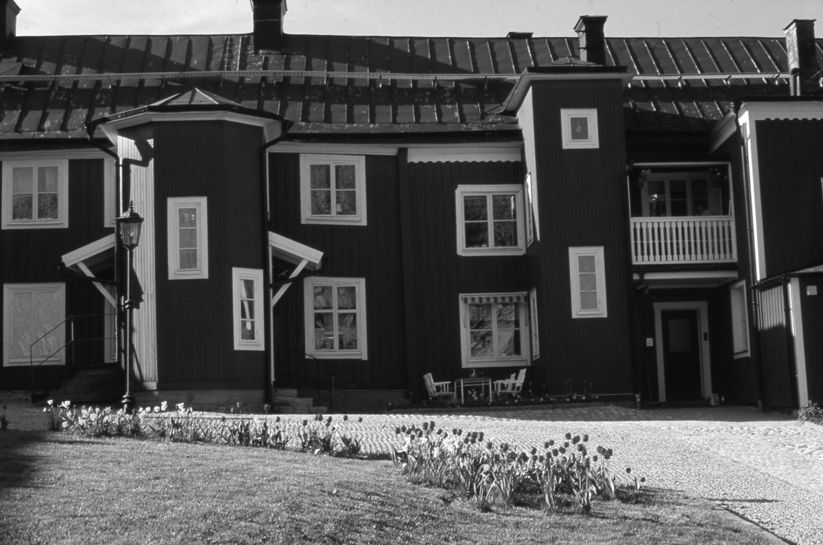Bostadshus på ågård på norr, Västerlånggatan 1. Tulpanerna blommar i rabatten och trädgårdsmöblerna är utställda.