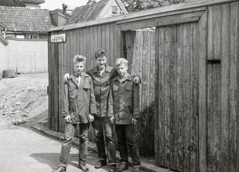 Kent, Sigurd og Roger Johansen kledd i Freia sjokoladejakker. Det var populært å selge sjokolade på idrettsstevner for å tjene penger og samtidig komme gratis inn. Andre barn på «haugen» jobbet med lotterisalg, leverte ut aviser eller solgte syrinbuketter når syrinene blomstret. (Foto/Photo)