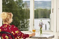 Dame i rød bluse som med ryggen til. Ser ut av vinduet ut mot elva.  Damen sitter på en stol og holder høyre hånd rundt et glass med eplemost som er plassert på et bord. En glassblomstervase med blomster