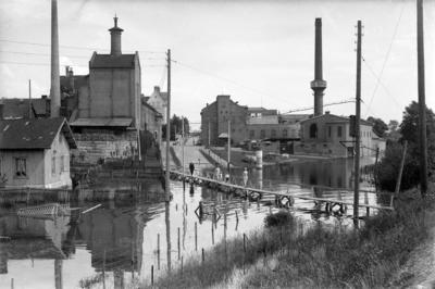 Svart-hvitt fotografi som viser en vannfylt gate med provisorisk bro over, et lite plankehus til venstre og to store murbygninger; Hamar bryggeri og melkefabrikken med en høy, rund mursteinspipe.. Foto/Photo