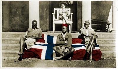 Kolorert bilde. Et norsk flagg er brettet ut over en trapp til en balkong, tre afrikanere sitter på flagget. En lys gutt sitter på en stol på balkongen.. Foto/Photo