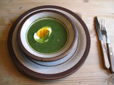 Neslesuppe med halvt egg servert i rustikk keramikkskål.