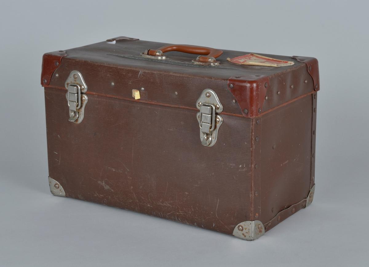 Koffert i papp med metallforsterkninger i hjørner, metallhåndtak på topplokk og metalllås på lokket - foran og bak.   Trelister i topp og lokk. Lærreimer som holder lokket på plass.  Lav skillevegg deler koffertrommet i to. Metallhylle med seks rom plasseres på trelister øverst i koffertrommet. I rommene på hylla ligger diverse utstyr som fiskepatalogen brukte i sitt arbeid, har fått egne undernummer.   I lokket er det festet en plasthylle med plass til ulike redskaper og utstyr.