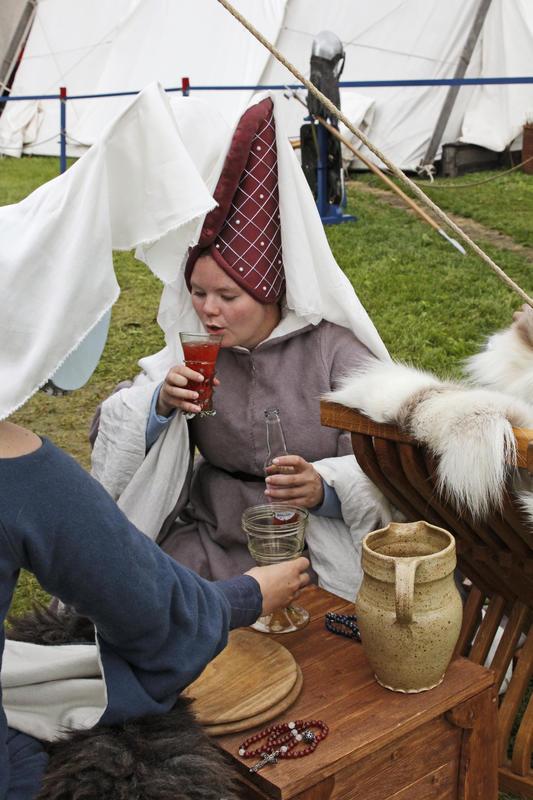 Middelaldersk adelsdame med høy hatt med slør nyter et glass drikke.