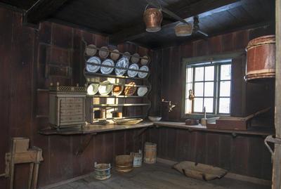 Interiør fra kjøkkenet i Skøienbygningen som viser en fullsatt tallerkenhylle i fire høyder og lyset som faller inn på porselenet gjennom et smårutete vindu. (Foto/Photo)
