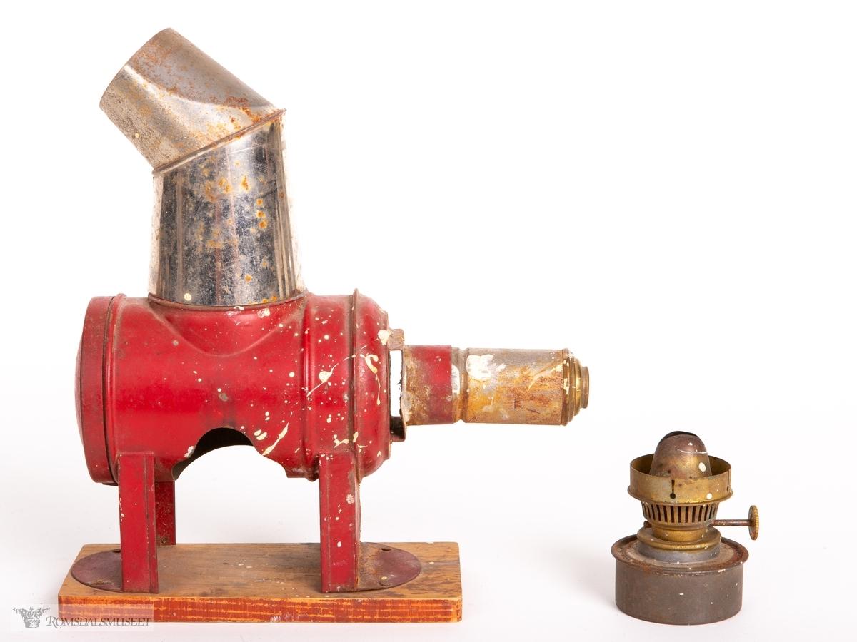 Projeksjonsapparat bestående av en tønneformet blikksylinder som står på to ben skrudd fast i en treplate. En hylse med en optisk linse på den ene enden med spor for innsetting av lysbilder. Hull under for isetting av oljelampe/lyskilde og avtagbar pipe i blikk på toppen. Parafinlampe i miniatyr følger med med brennerhode og en liten tank for parafin.