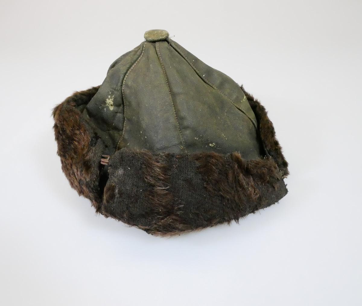 Rund lue sydd sammen av seks trekantete stoffdeler. På bunnen er det en pelskant som består av to deler som er brettet opp. De to delene er festet sammen med to metallhekter. Lua er foret med et gulnet bomullsstoff.