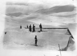Bergensbanens anlegg; to skiløperpar på taket av en anleggsb
