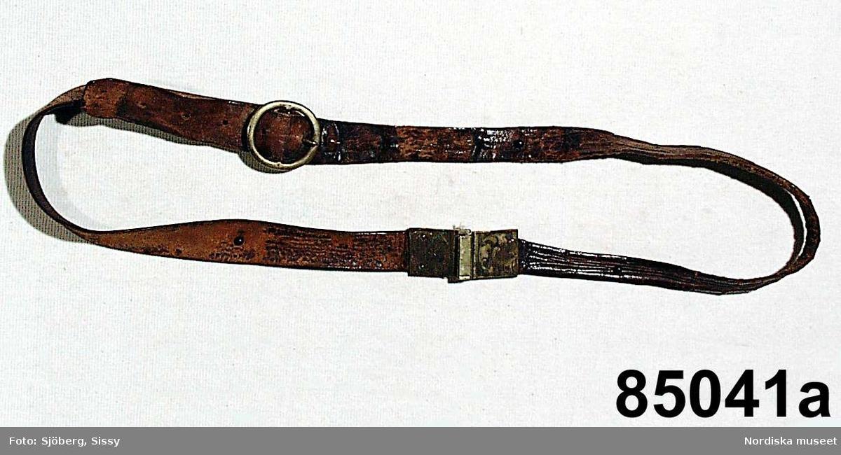 """Huvudliggaren: """"Minnen efter professor Frithiof Holmgren. a) Läderskärp med mässingsspännen och vidhängadne knif i slida. b) Tobakspung med pipa. Pipan stämpel 'GENERAL'. c) Ett par glasögon i fodral. Fodralet stämpel: 'J.  L. ROSE UPSALA IMPORTERAD'. d) Pinecnez. e) Börs, gråbrun med nickelgarnityr, innehållande 5 mynt. f) Linjal längd 43 cm, bredd 5,5 cm. Af trä. Svartmålad med pärlbroderi. g) 2 st nycklar med vidhängande träklamp, å hvilken läses: 'Akademi Sprutan No 2'."""""""