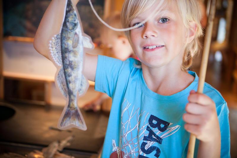 Glad gutt har fått fisk inne på Besøkssenter våtmark