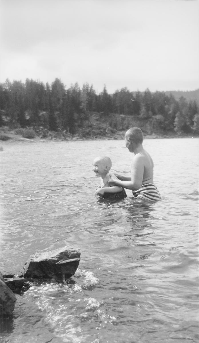 En eldre gutt hjelper en yngre gutt med svømmetrening i en innsjø på østlandet. Den yngste gutten har på svømmebelte.